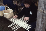 Woman weaving a white oak basket, probably at an event to promote the opening of a southern folk...