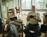 Eugene Forbes and Jeff Sheppard singing from the Lloyd's hymnal on the porch during the Camp...