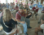 Dennis George playing the fiddle at a social hosted by Coy and Marie Ivey on their property in...