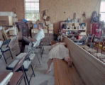 Woman lying on a pew at a social hosted by Coy and Marie Ivey on their property in Henagar,...