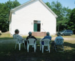 Local citizens sitting outside the church building, listening to the Mount Pisgah Cooper Book...