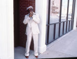 Jerry McCain playing a  harmonica on a downtown sidewalk.