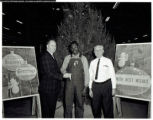 Ed Locke and Jasper Buckner presenting an award to a Continental Gin  Company employee at a company Christmas party.