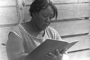 Minnie B. Guice making notes in a book while bags of cotton are being weighed.
