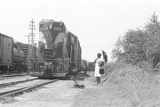 Woman walking beside a long train on the railroad tracks near Newtown, a neighborhood in...