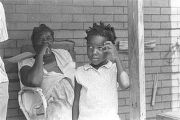 Young girl on the front porch of a house in Newtown, a neighborhood in Montgomery, Alabama.