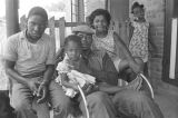 Man and children on the front porch of a brick house in Newtown, a neighborhood in Montgomery,...