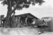Children playing on a make-shift seesaw in the dirt yard in front of a brick house in Newtown, a...