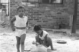 Two little girls playing in the dirt yard in front of a brick house in Newtown, a neighborhood in...