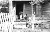 Two children on the front porch of a clapboard house in Newtown, a neighborhood in Montgomery,...