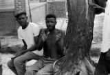 Two men seated in front of a tree in the dirt yard beside a house in Newtown, a neighborhood in...