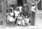 Group of children and adults on the front porch of a brick house in Newtown, a neighborhood in...