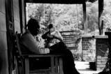 Man seated in a wooden chair on the front porch of a house in Newtown, a neighborhood in...
