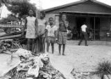 Children standing in the dirt yard in front of a brick house in Newtown, a neighborhood in...