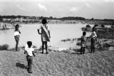 "Woman and children standing on the bank of ""The Big Ditch,"" a gravel quarry filled with..."