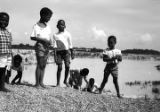 "Children standing on the bank of ""The Big Ditch,"" a gravel quarry filled with water near..."