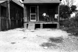 Three children on the front porch of a small clapboard house in Newtown, a neighborhood in...