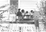 Four children seated on a glider on the front porch of a clapboard house in Newtown, a...