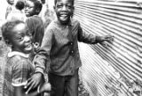 Group of children beside a building made of corrugated metal in Newtown, a neighborhood in...
