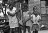 Four children standing next to a fence in front of a brick house in Newtown, a neighborhood in...