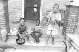 Three children on the front porch of a clapboard house in Newtown, a neighborhood in Montgomery,...