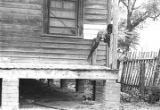 Young boy on the front porch of a wooden house in Newtown, a neighborhood in Montgomery, Alabama.