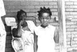 Woman and little girl on the front porch of a house in Newtown, a neighborhood in Montgomery,...