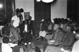 Stokely Carmichael speaking at a meeting at a small church building.