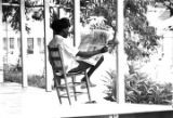 Woman reading The Southern Courier while seated on a wooden chair on the porch of a house in...
