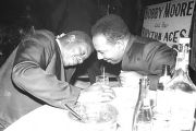 Two men seated at a table at the Laicos Club in Montgomery, Alabama, during a performance by Bobby...