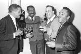 Roscoe Williams, Bobby Moore, and two other men standing around a pay telephone at the Laicos Club...