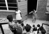 Two women speaking to children seated on the steps outside a brick building, possibly during a...