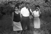 "Young man and two young women standing in the grass beside a road, observing the ""March..."