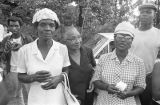 "Three women standing in front of a car parked beside a road during the ""March Against..."