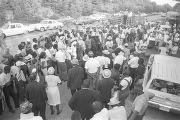 "Crowd gathered on the side of a road during the ""March Against Fear"" begun by James..."