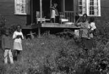 "Woman and children in the yard in front of a small house, probably observing the ""March..."