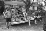 "Group of white people sitting or leaning on the hood of a truck, observing the ""March Against..."