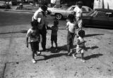 Man and children on the sidewalk at the intersection of two streets in Harlem.