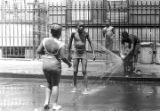 Children playing in the water from a fire hydrant on a street in Harlem.