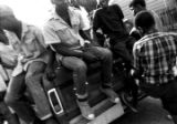 Several young men sitting on or standing around the back of a pickup truck parked at a convenience...