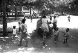 Adults and children around a concrete tunnel in a park in Harlem.