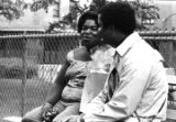 Norman Lumpkin talking to a woman while seated on a bench in front of a chain-link fence in Harlem.