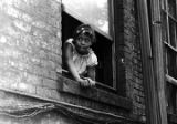 Girl leaning out the upper-story window of a brick apartment building in Harlem.
