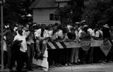 Young men and women lined up behind a barricade during a civil rights demonstration in Greensboro,...