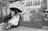 Woman sitting on a chair on the sidewalk in front of a brick building in Harlem.