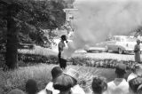 Man spraying tear gas at a group of young men and women during a civil rights demonstration in...
