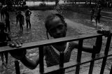 Little girl standing at the fence around a wading pool in Harlem.