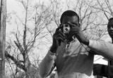 Young man taking a photograph while marching to the courthouse in Greenville, Alabama, during a...