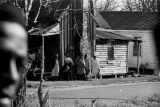 People standing outside a house near Harrison Street Baptist Church in Greenville, Alabama, before...