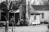 People standing outside a house near a small rural church building in Greenville, Alabama, before...